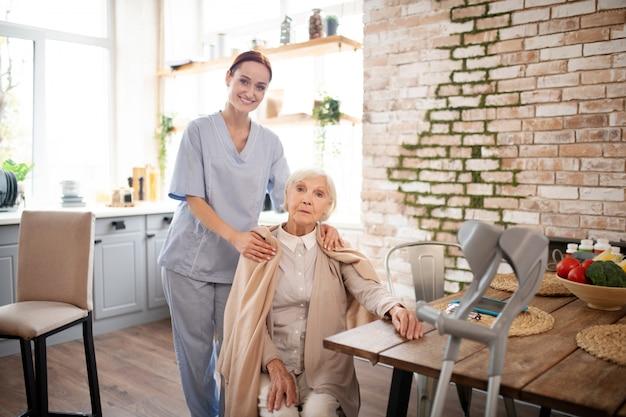 Hilfreiche rothaarige krankenschwester, die in der nähe der alten frau steht