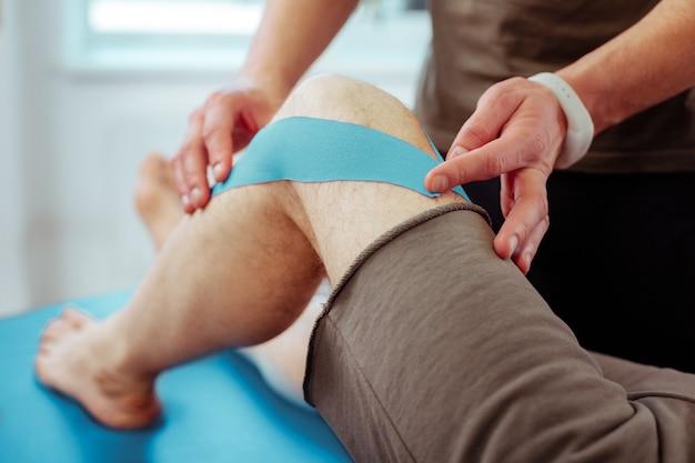 Hilfreiche therapie. hände eines professionellen, erfahrenen männlichen arztes beim berühren des patientenbeins patients