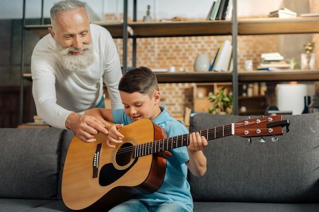 Hilfreiche tipps. angenehmer, liebevoller großvater, der seinem enkel im teenageralter einen rat gibt, wie man akkorde richtig spielt, während der junge lernt, wie man gitarre spielt