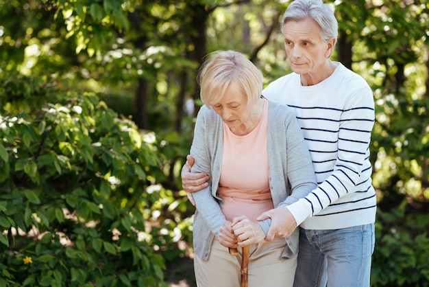 Hilfreicher, aufmerksamer mann, der sich um seine alte frau kümmert und ihr hilft, schritte zu machen, während er im park spazieren geht