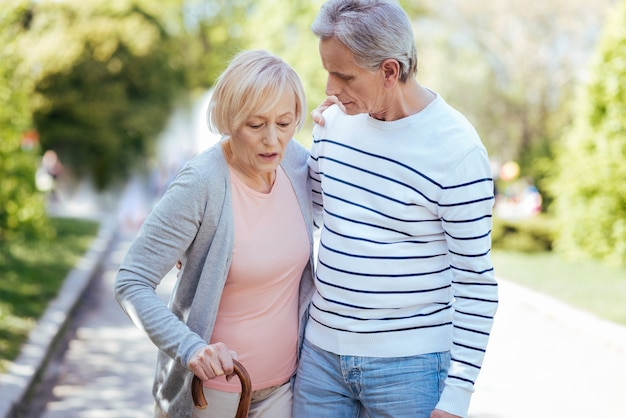 Hilfreicher fürsorglicher erfahrener mann, der sich um seine alte frau kümmert und ihr hilft, schritte zu machen, während sie auf der straße geht
