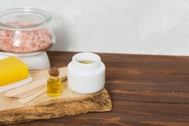 Himalaya-steinsalz im glas; holzstäbchen aus wachs; honig; gelbe kräuterseife und flasche des ätherischen öls auf tabelle