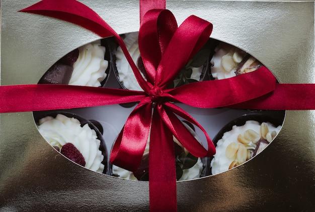Himbeer-schokoladenkuchen mit schlagsahne in einer geschenkbox