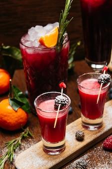 Himbeer schoss cocktails mit tannenzapfen auf dem holzschreibtisch auf dem tisch im restaurant