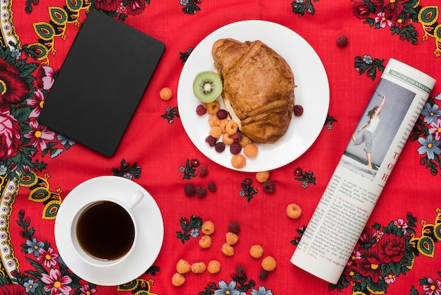 Himbeere; kiwi und croissant auf teller mit kaffeetasse; tagebuch und aufgerollte zeitung auf tischdecke