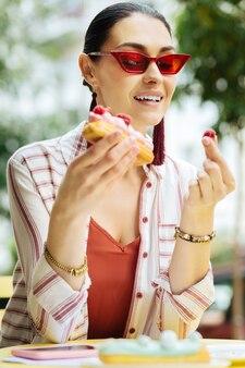 Himbeeren betrachten. fröhliche entspannte frau, die rote brille trägt und die himbeere in ihrer hand betrachtet, während sie ein dessert in einem café isst