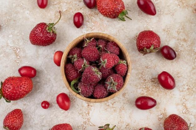 Himbeeren in der holzschale mit den hüften und den erdbeeren, die auf marmorhintergrund verstreut werden. hochwertiges foto