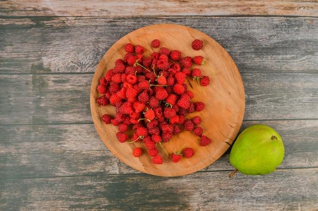 Himbeeren mit zitrone auf einem hölzernen hintergrund. holzblöcke mit den worten vitamin c, frisches obst im hintergrund, gesundes essen oder diätkonzept. von oben betrachten. ein ort zum schreiben.