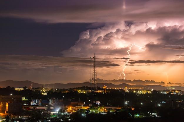 Himmel mit blitzschlägen hügeln hinter kleinstadt