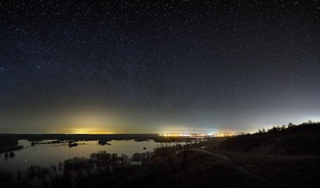 Himmel mit den sternen in der landschaft mit einem teich. nachtlandschaft mit see.