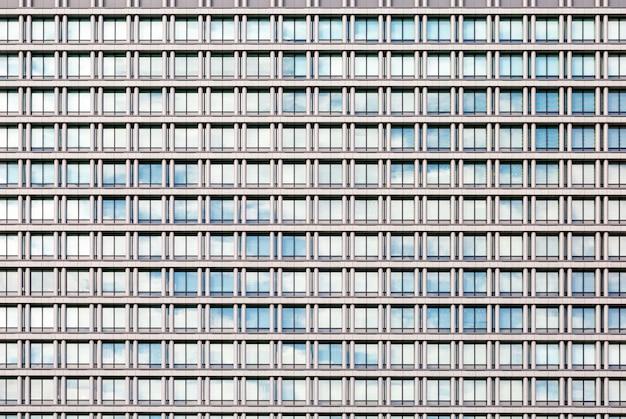 Himmel und wolken reflektierten sich in einer glasfassade des modernen gebäudes