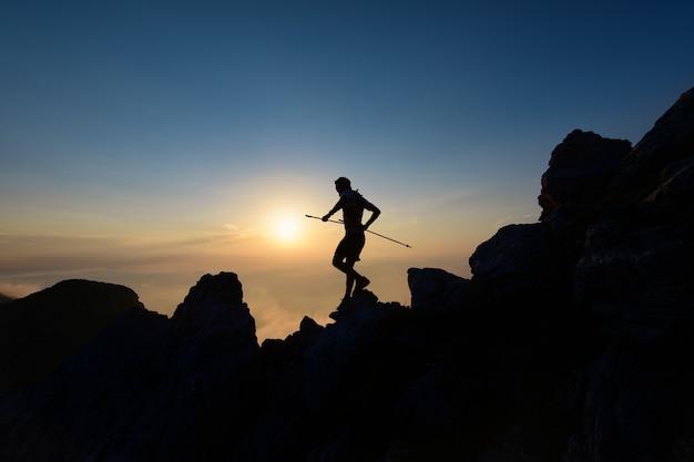 Himmelsläufer in der silhouette bei sonnenuntergang unter den felsen