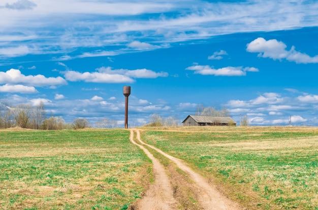 Himmelsstraße auf dem feld, die zur schuppenscheune und zum wasserturm der ländlichen landschaft des dorfes führt.