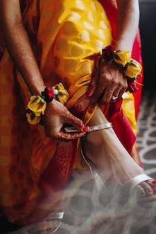 Hindu-braut setzt traditionelles armband auf ihr bein