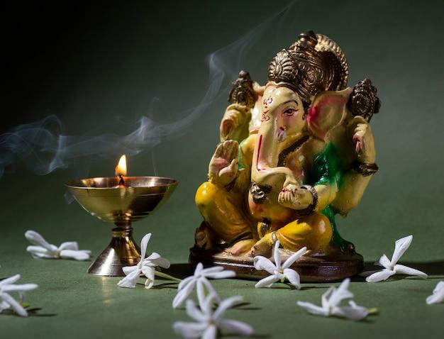 Hindu-gott ganesha. ganesha idol. eine bunte statue von ganesha idol auf dunklem hintergrund. platz für text oder überschrift.