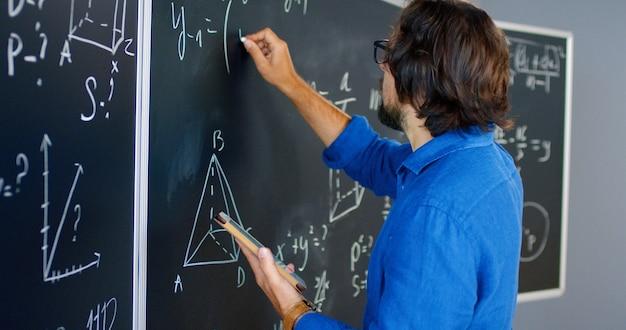 Hinten auf kaukasischen männlichen lehrern in gläsern, die an bord im klassenzimmer stehen und physik- oder geometriegesetze zum unterricht sagen. schulkonzept. pädagogische mathematik lektion. rückansicht des dozenten.