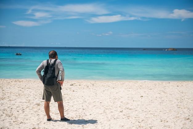 Hinten des alten älteren pensionierten mannes auf weißem sandstrand betrachten türkisfarbenes krystrales andamanenmeer und blauen himmel auf similan-insel, phang nga, thailand. rentner reisen im sommer.