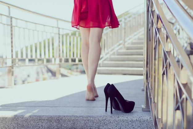 Hinten hinter dem rücken nahaufnahme foto von sexy fit schlanke lange sexuelle verführerische verführerische beine konzept. schönes sorgloses hübsches glückliches mädchen, das ihre schwarzen stilettos auf der straße zurücklässt, die in die sonne geht