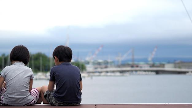 Hinter bildern der familie, die vor dem hafenhafen oder dem seedock in otaru hokkaido japan sitzt