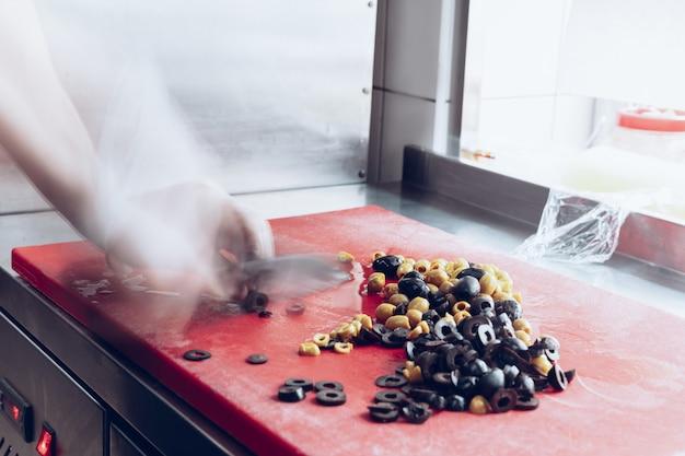 Hinter den kulissen der marken. der küchenchef kocht in einer professionellen küche ein restaurantessen für den kunden oder die lieferung. öffnen sie das geschäft von innen. mahlzeiten während der quarantäne. beeilung, bewegung.