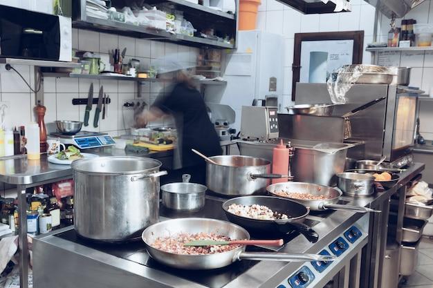 Hinter den kulissen der marken. der küchenchef kocht in einer professionellen küche ein restaurantessen für den kunden oder die lieferung.