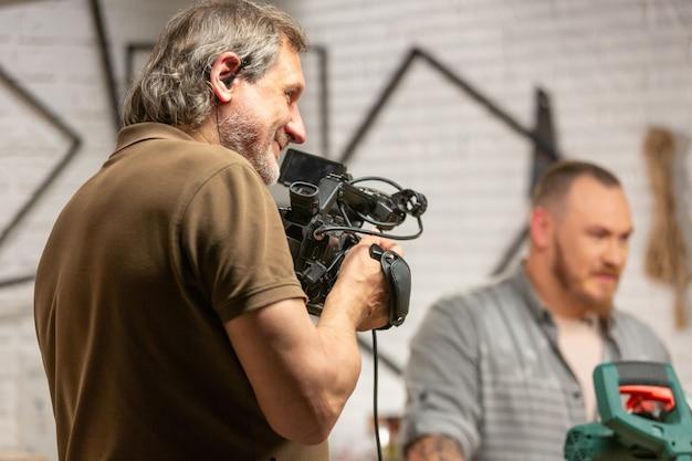 Hinter den kulissen der produktion für videoaufnahmen mit kameraausrüstung die kulisse mit dem arbeiter