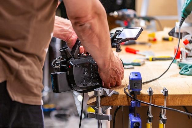Hinter den kulissen der produktion für videoaufnahmen von kameraausrüstung die kulisse mit dem arbeiter