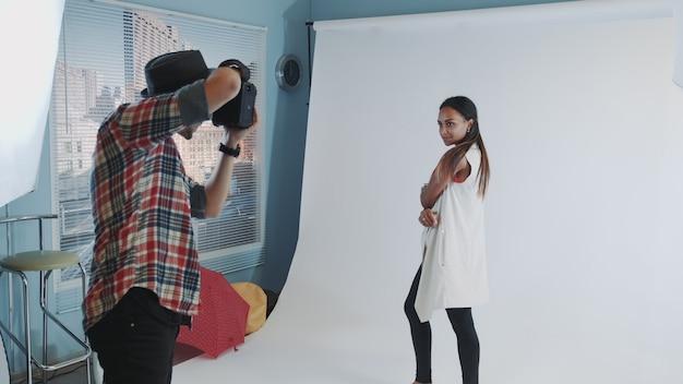 Hinter den kulissen des fotoshootings: professioneller fotograf, der im studio arbeitet, indem er fotos von einem schwarzen model macht