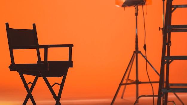 Hinter den kulissen mit dem regiestuhl, der einen videofilm filmt, während das produktionsteam die bühne aufbaut