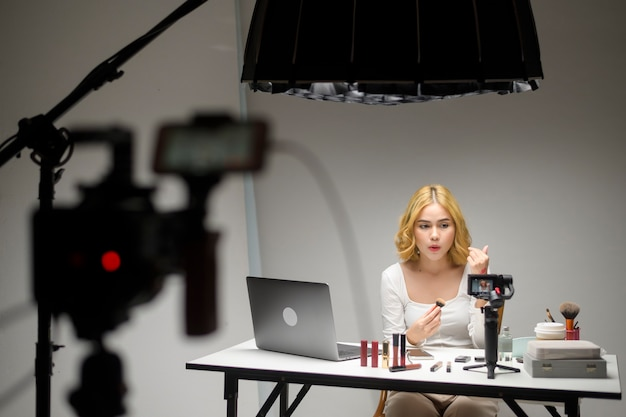 Hinter den kulissen präsentiert junge blonde unternehmerin, die mit laptop arbeitet, kosmetikprodukte während des online-live-streams auf weiß