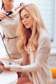 Hinter den kulissen. schöne junge frau, die zeitschrift liest, während friseurin ihr haar mit lockenstab im make-up-raum kräuselt?