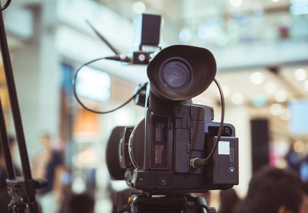 Hinter der videokamera werden filmaufnahmen der eröffnung im konferenzsaal gemacht. live-streaming-mikrofon