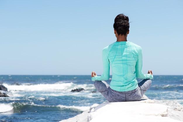 Hinter der yogafrau am strand