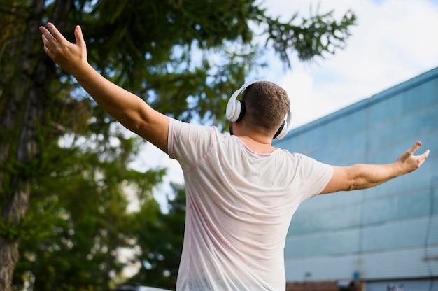 Hinter einem jungen mann mit erhobenen händen