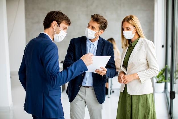 Hinter ihnen arbeiten zwei junge männer und frauen, die mit papier in händen drinnen im büro mit jungen leuten diskutieren