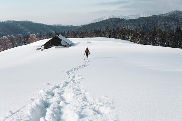 Hinter schuss einer person, die im schneebedeckten berg nahe einem alten häuschen wandert, das von tannenbäumen umgeben wird
