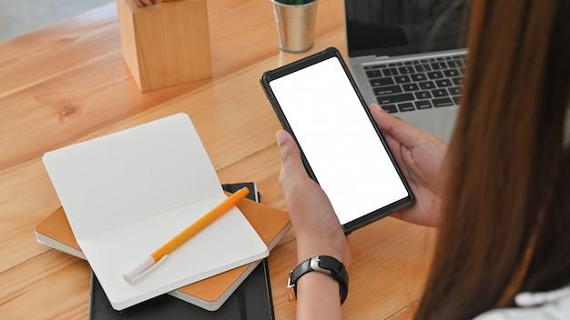 Hinteransicht beschnittener schuss der jungen frau beim verwenden des weißen leeren bildschirm-smartphones am schreibtisch im büro.