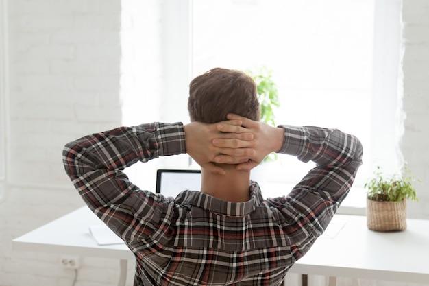 Hintere ansicht am entspannten mann, der von der arbeit über laptop stillsteht