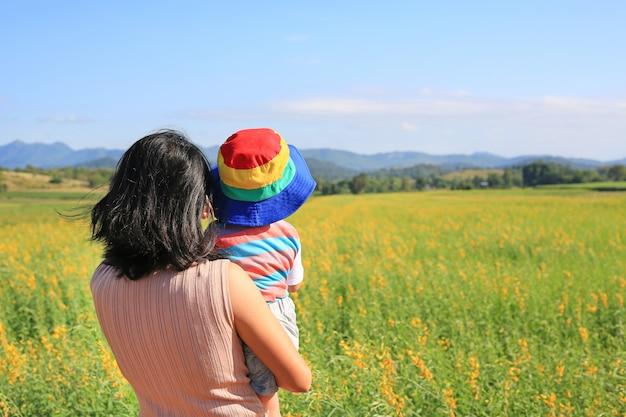 Hintere ansicht asiatische mutter, die baby am sunnhemp-hangfeld trägt und berge am sonnigen tag herausschaut.