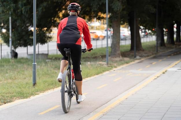 Hintere ansicht der älteren frau, die fahrrad im freien mit kopienraum reitet