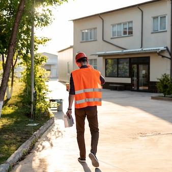 Hintere ansicht der arbeitskraft mit schutzausrüstung