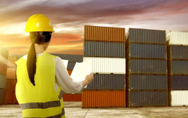 Hintere ansicht der asiatischen arbeitnehmerin mit der sicherheitsweste und schutzhelm, die ein papier überprüft den versand auf dem dock halten