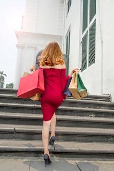 Hintere ansicht der asiatischen frau in tragenden einkaufstaschen der roten kleidung