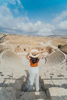 Hintere ansicht der asiatischen jungen frau, die vor römischem südtheater, jerash, jordanien steht