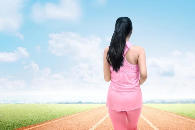 Hintere ansicht der asiatischen läuferfrau laufend auf der laufbahn
