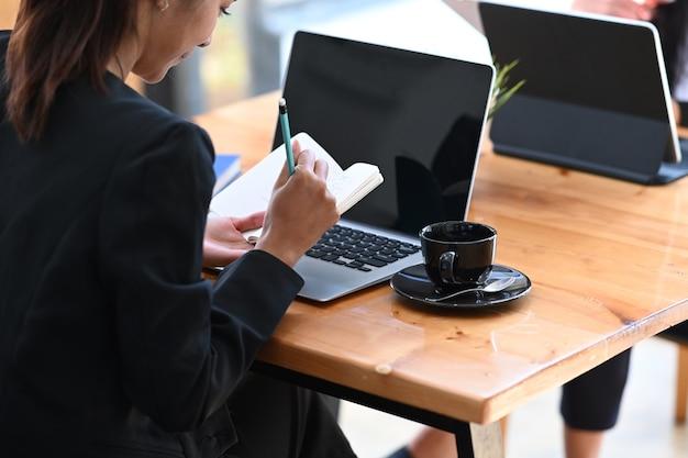 Hintere ansicht der attraktiven geschäftsfrau im anzug, die vor laptop-computer sitzt und notiz im notizbuch macht.