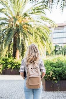 Hintere ansicht der blonden jungen frau mit ihrem rucksack