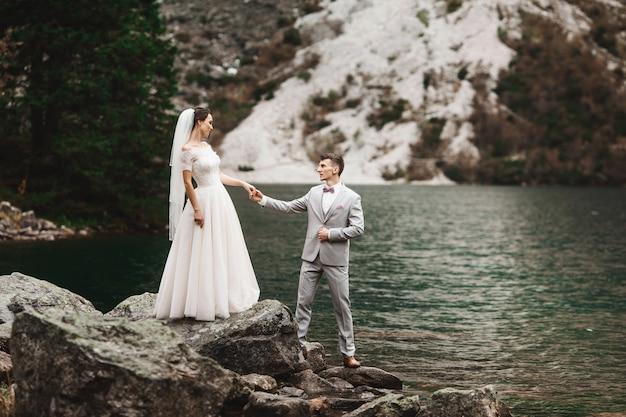 Hintere ansicht der braut und des bräutigams, stehend auf dem seeufer mit szenischem bergblick in polen, morskie oko