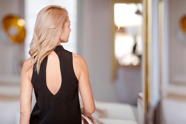 Hintere ansicht der elegant gekleideten jungen frau im schönheitssaloninnenraum; hintere ansicht der dünnen geschäftsfrau auf den hohen absätzen, die innen stehen. kopieren sie platz