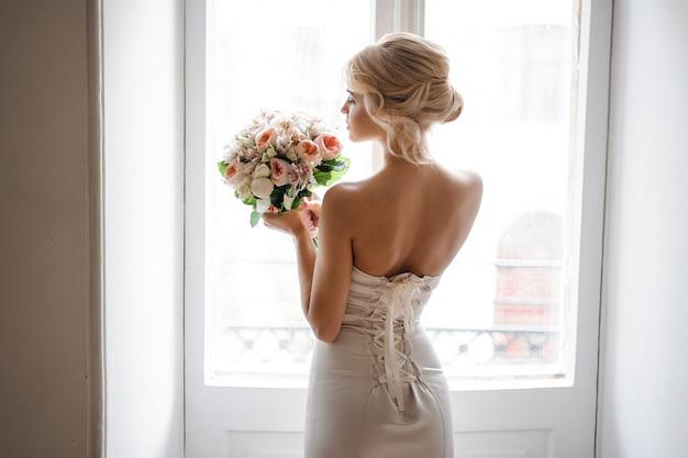 Hintere ansicht der eleganten blonden braut kleidete in einem weißen kleid an, das einen hochzeitsblumenstrauß hält
